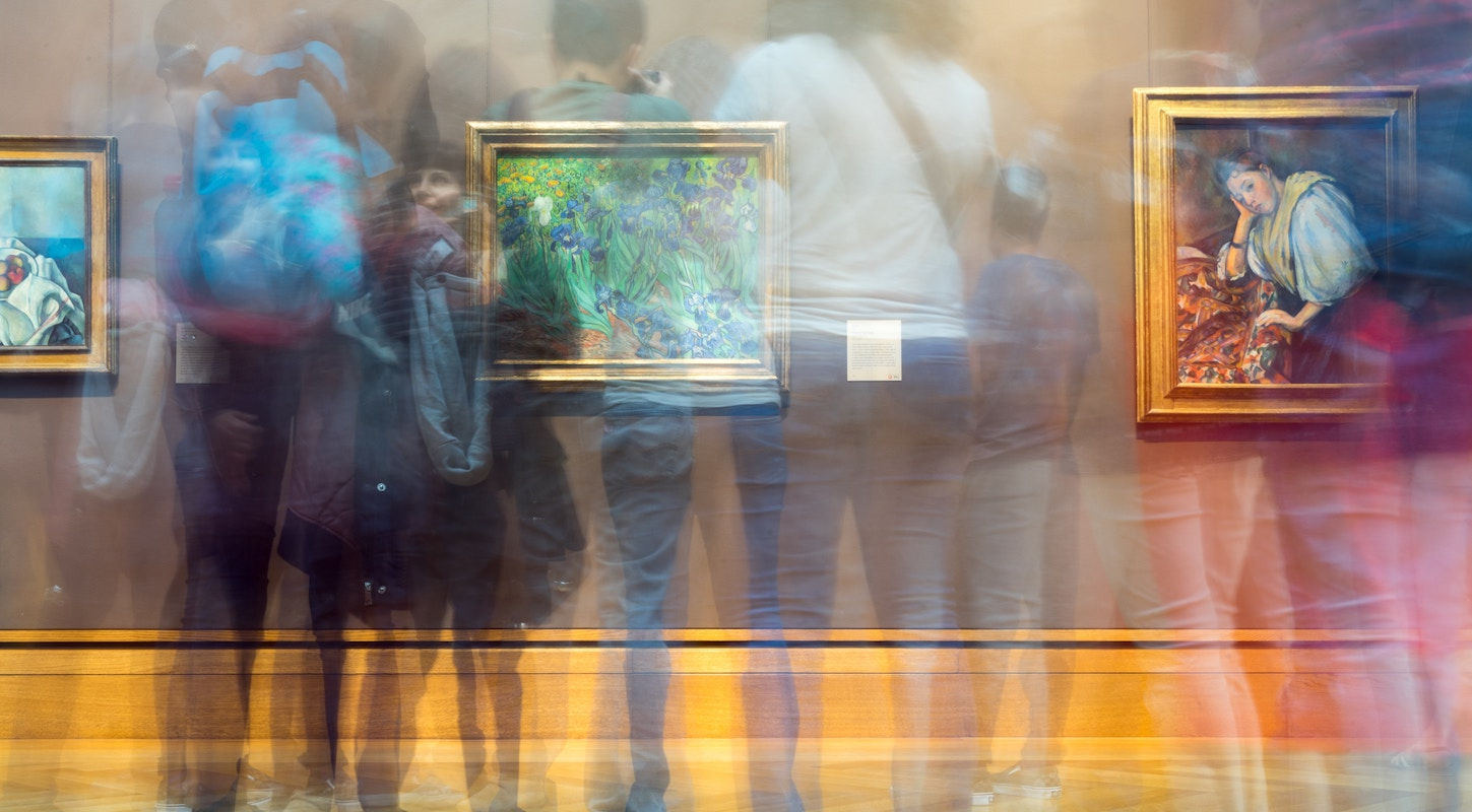 People gathering inside painting exhibit. Photo by Sergei Akulich on Unsplash